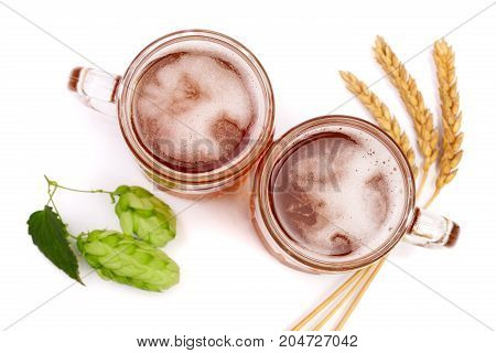 glass of foamy beer with hop cones and wheat isolated on white background. Top view.