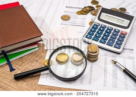 Magnifying Glass With Financial Documents, Coin, Notepad, Calculator And Pen