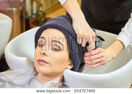 Girl at the hairdresser, towel. Hair salon client, sink.