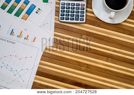 Business Charts And Graphs With Laptop, Cup Of Coffee, Calculator And Pen
