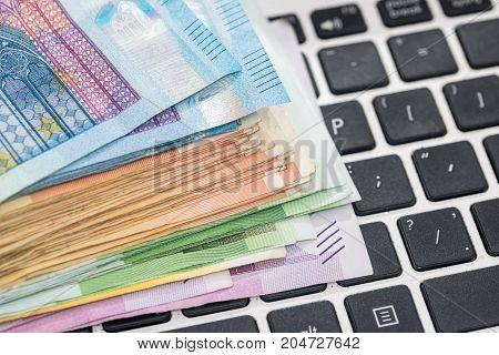 euro money on laptop . close up