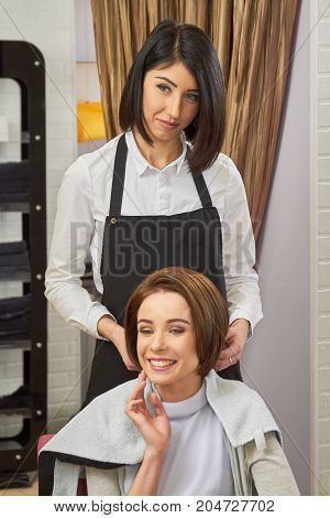 Woman at the hairdresser smiling. Happy hair salon customer. Which haircut suits you best.