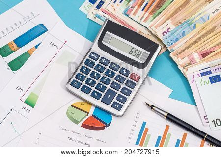 Business Graph With Euro Banknote And Calculator On Blue Background