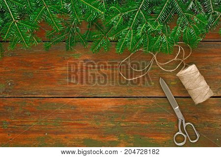 Christmas DIY background. Scissors and string jute on rustic wood with fir tree branches border. Handmade hobby and winter holidays concept, top view, copy space.