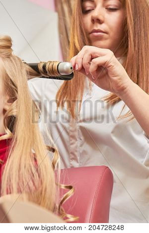 Hairstylist using curling iron. Hairdresser is working.