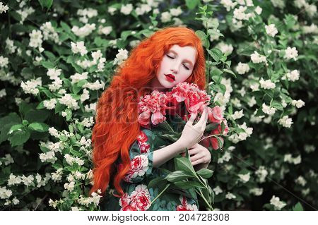 Beautiful red-haired girl with beautiful curly hair with pale skin in a  beautiful summer dress. Beautiful model. Beautiful woman on red roses garfen, Beautiful nice girl