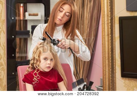 Cute child getting hair done. Hairdresser with curling iron. Generation of fashion.