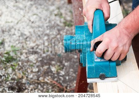 Close up hands of carpenter working with electric planer on wooden plank in carpentry workshop