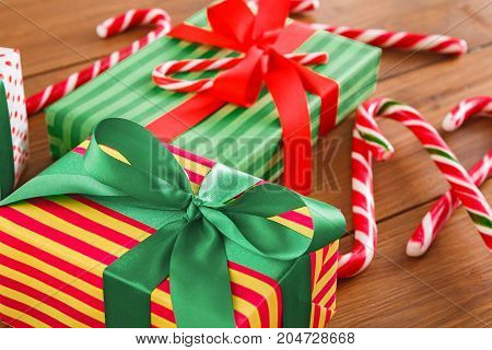 Gift box wrapped in colorful striped paper. Christmas, new year and winter holidays concept. Crop, closeup