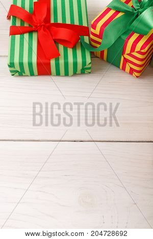 Creative presents border background. Colorful gift boxes in striped wrapping paper for any holiday decorated with ribbon bows on white wood with copy space.