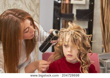 Little girl and female hairdresser. Stylist holding hairspray bottle.