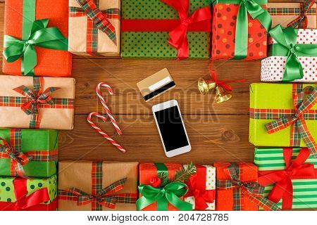 Lots of Gift boxes, xmas bells, xmas candy on wood background top view, flat lay. Presents in craft and colored paper decorated with red and green ribbon bows. Mobile phone, card.