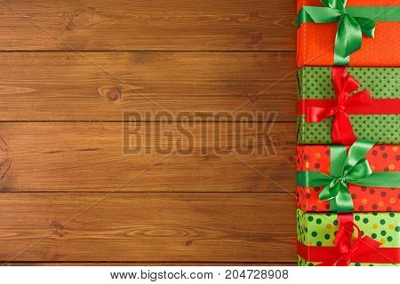 Traditional presents in craft and colored paper decorated for any holiday concept. Gift boxes, top view with copy space on wood table background.