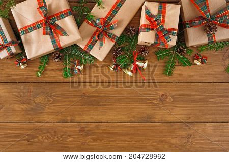 Creative presents in craft and grey paper decorated for any holiday concept. Gift boxes frame, fir tree branch, top view with copy space on rustic table background.