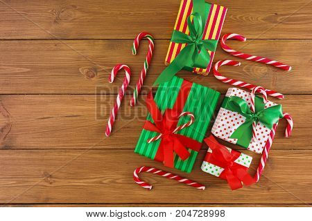 Gift boxes, top view on wood table background. Border of colored packages with red, green ribbons for christmas, valentine day or birthday