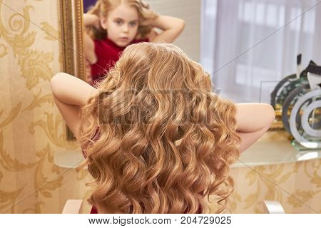 Hair of a little girl. Beautiful blonde wavy hair.