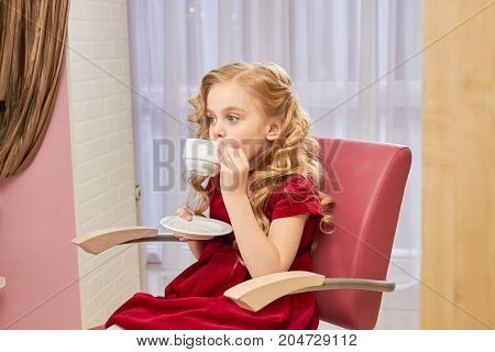 Little girl drinking coffee. Child holding cup and saucer.
