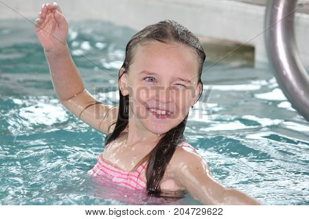 Young girl-child playing in and, having fun in a swimming pool.