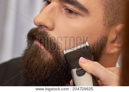 Face of bearded man, trimmer. Beard trimming, close up.