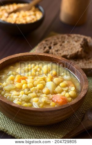 Vegetarian and vegan yellow split pea soup or stew with potato carrot and celery in wooden bowl photographed with natural light (Selective Focus Focus in the middle of the soup)