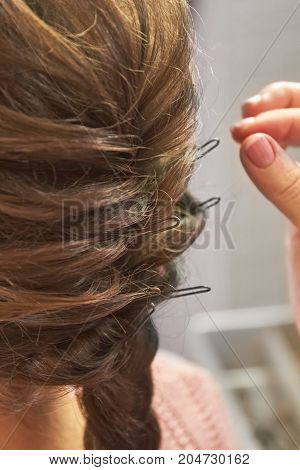 Braided female hairdo. Hair with bobby pins, macro. poster
