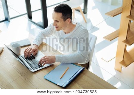 My favourite occupation. Joyful positive nice man sitting at the table and working on the laptop while enjoying his occupation