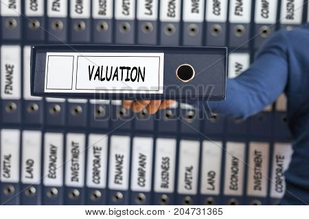 Valuation Concept. Business Concept. Young Man Holding Ring Binder.