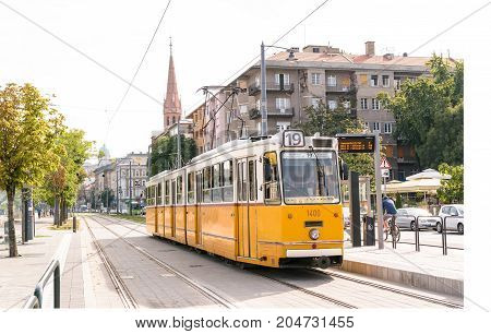 Image of one of the old yellow trams in Budapest, Hungary, stopping at a station.