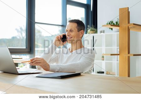 Confident manager. Happy delighted nice man holding a pencil and pointing at the laptop screen while talking on the phone
