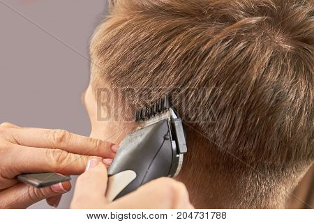 Hands using hair clipper. Guy getting haircut close up.