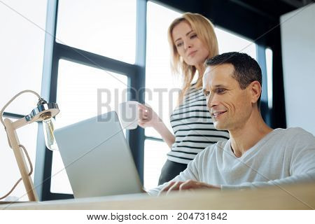 Office work. Positive nice smart woman standing behind her colleague and holding a cup of tea while looking at the laptop screen