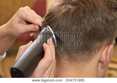 Man getting haircut, close up. Comb and hair clipper.