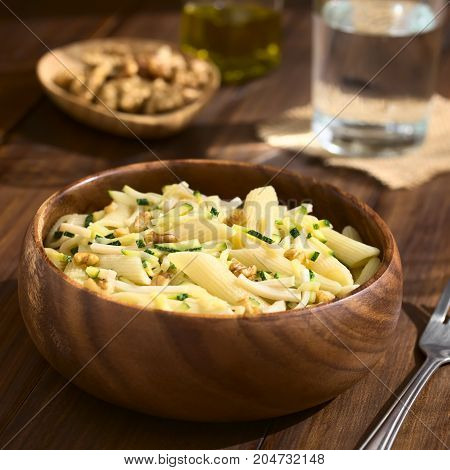 Penne pasta with zucchini and ham stripes and walnut served in wooden bowl photographed on dark wood with natural light (Selective Focus Focus in the middle of the dish)