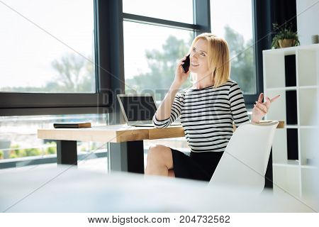 Work issues. Attractive smart confident businesswoman smiling and talking on the phone while discussing business issues
