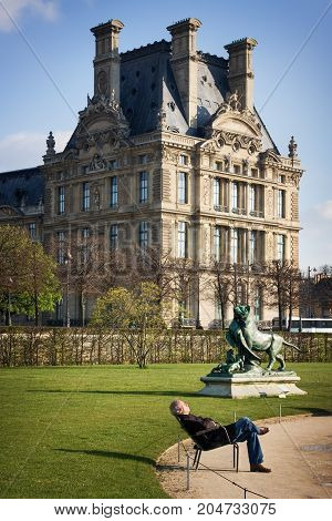 France, Paris - Spring 2008: Tourist is relaxing on a bench In the park in front of the Louvre. View from Avenue du General Lemonnier to Jardin des Tuileries. Paris. France