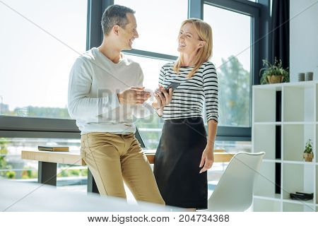 Positive mood. Happy joyful nice colleagues looking at each other and laughing while being in a positive mood