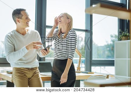 Great joke. Happy positive cheerful woman standing together with her colleague and laughing while listening to his jokes