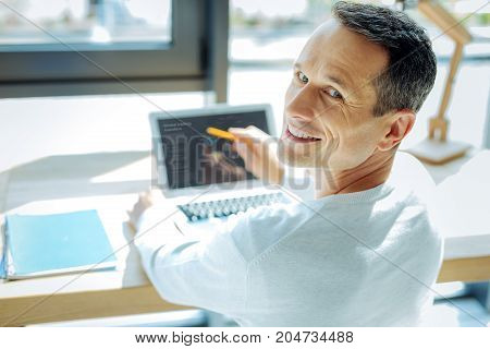 Professional businessman. Delighted positive nice man smiling and turning to you while pointing at the laptop screen
