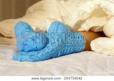 Female Feet In Woolen Blue Socks. Lie On Each Other