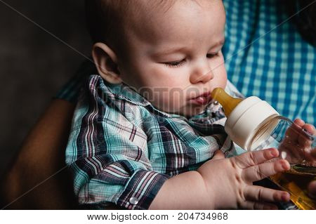 father's hand holding baby boy eating from the bottle
