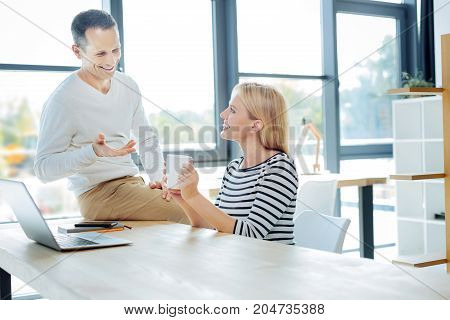 Informal behaviour. Delighted cheerful handsome man sitting on the table and smiling while telling a joke to his colleague