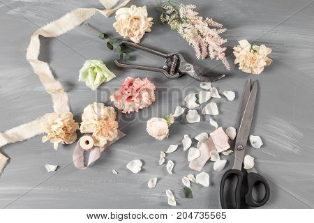 flowers and garden tools. The florist work table with accessories gray background