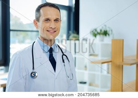 Healthcare system. Joyful confident nice doctor wearing a labcoat and smiling to you while being ready to treat his patients