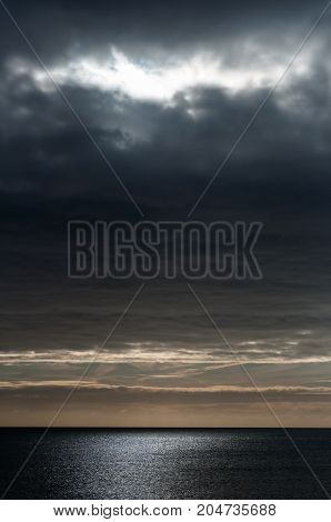 Seascape as night approaches with grey clouds in a dark moody sky and light rays softly scattering light on water.