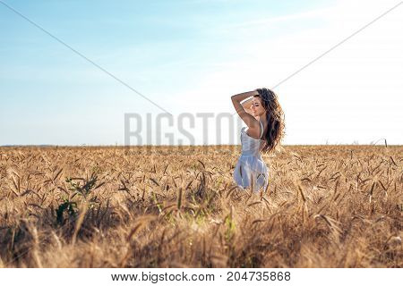 Beautiful happy woman in a field, sunny afternoon, white dress. Brunette hair, tanned skin, concept of enjoying nature. Happy smiling. Harmony with wheat.