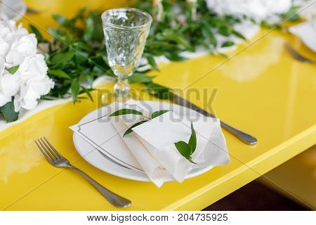 Candles and goblets on a decorated wedding table. yellow green white color. Style lemon