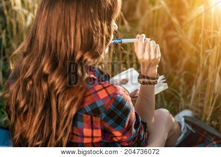 Beautiful happy girl in the field, sunny day shirt. Concept new ideas, writing in notebook. enjoyment of nature. Rest on the air.