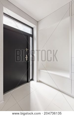 Elegant home interior with white entryway and black door