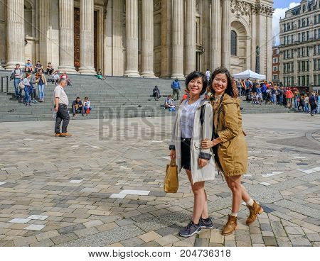 St. Paul's London UK - August 3 2017: Two girls posing for a photograph outside St. Paul's Cathedral. They are smiling while they pose in the foreground.