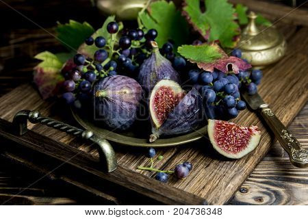 ripe figs and grapes on a wooden tray